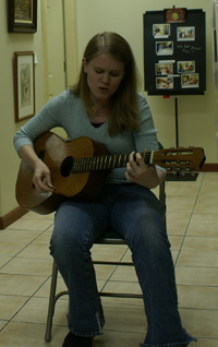 Mandy Rakow plays guitar at exhibit